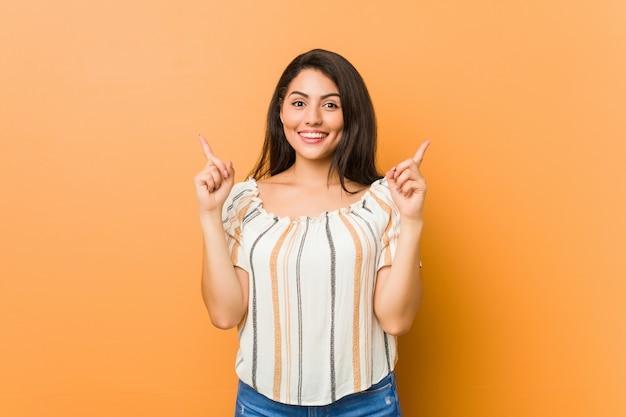 Молодая соблазнительная женщина показывает обоими пальцами на носу вверх, показывая пустое пространство.
