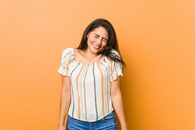 若い曲線の女性は笑って目を閉じて、リラックスして幸せを感じています。