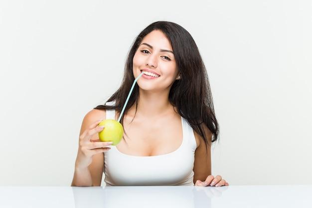 Молодая испанская женщина пьет яблочный сок с соломой