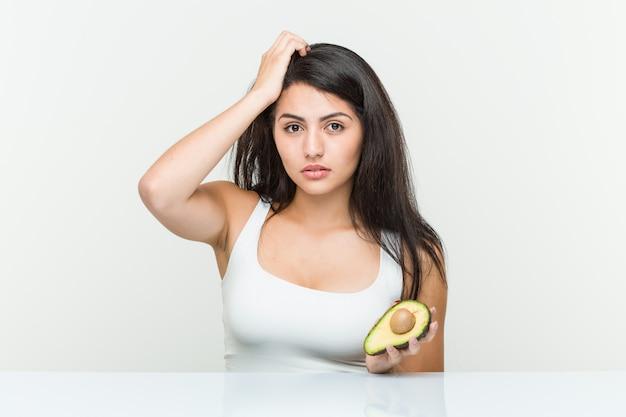 Молодая испанская женщина, держащая авокадо в шоке, она вспомнила важную встречу.