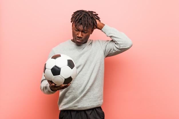 ショックを受けているサッカーボールを保持している若いフィットネス黒人男性、彼女は重要な会議を覚えています。