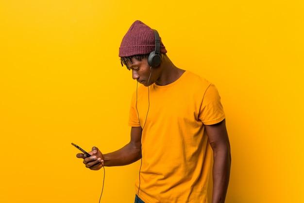 携帯電話で音楽を聞いて帽子をかぶって黄色に対して立っている若いアフリカ人