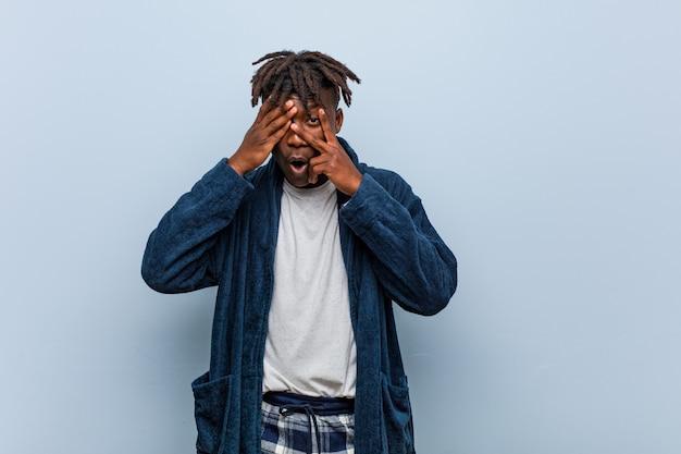 パジャマを着ている若いアフリカ黒人男性は、恐怖と緊張の指の間で点滅します。