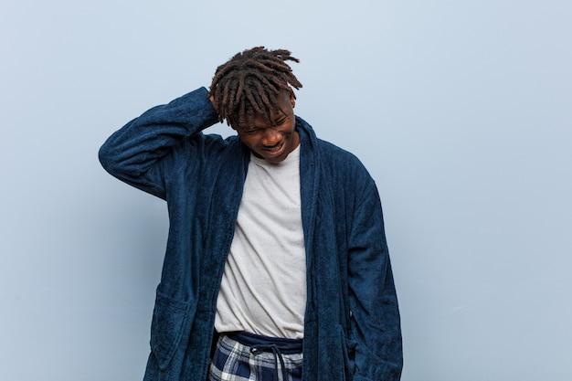 座りがちな生活のため首の痛みに苦しんでいるパジャマを着ている若いアフリカ黒人男性。