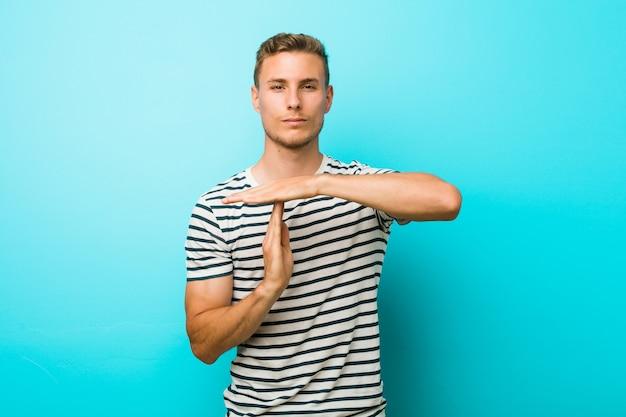 タイムアウトジェスチャーを示す青い壁に若い白人男。