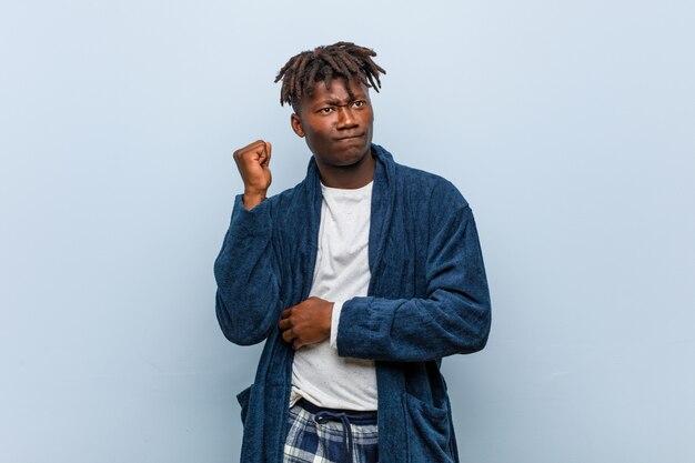 頭の後ろに触れる、考えて、選択をするパジャマを着ている若いアフリカ黒人男性。