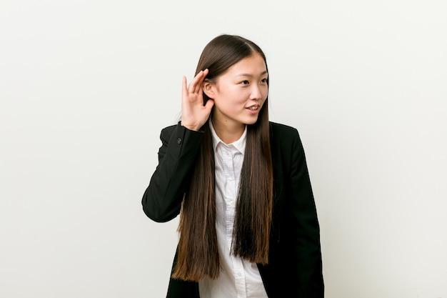 ゴシップを聞いてしようとしている若いかなり中国ビジネス女性。