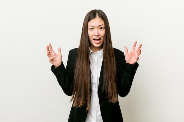 Молодая милая китайская бизнес-леди кричащая с яростью.