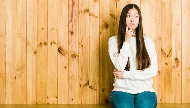 疑わしいと懐疑的な表情で横向きの木製の場所に座っている若い中国人女性。