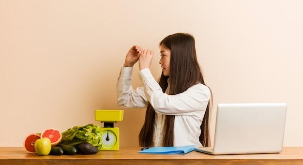 若い栄養士の中国人女性が彼の額に手をつけて遠くを見ている彼女のラップトップで働いています。