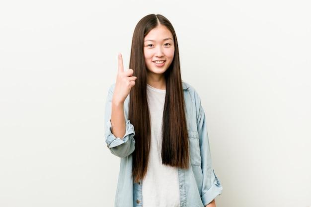 指でナンバーワンを示す若いアジア女性。