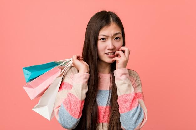 Молодая азиатская женщина держа ногти хозяйственной сумки сдерживая, слабонервный и очень тревоженый.