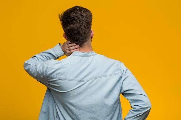 Молодой красивый студент носить джинсовые рубашки сзади думать о чем-то.
