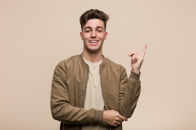Молодой кавказский человек нося коричневую куртку усмехаясь жизнерадостно указывая с указательным пальцем прочь.