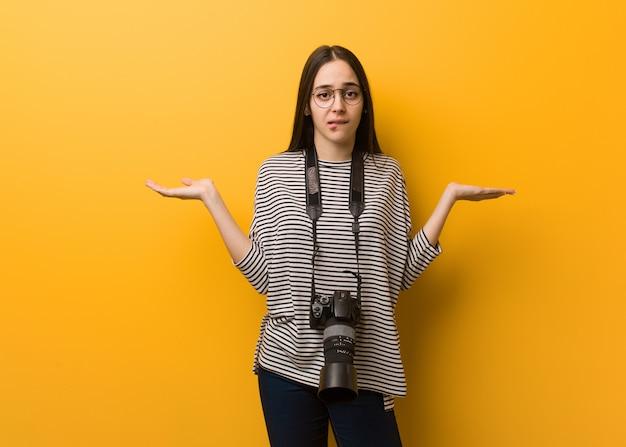 Молодой фотограф женщина смущена и сомнительна
