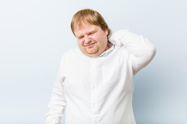 座りがちな生活のために首の痛みに苦しんでいる若い本物の赤毛のデブ男。