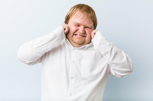 手で耳を覆う若い本物の赤毛のデブ男。
