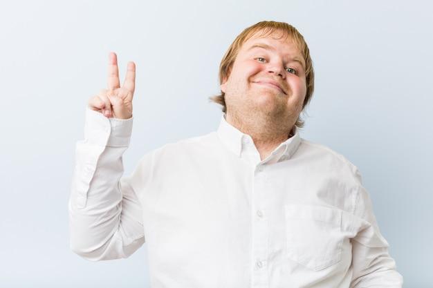 指で平和のシンボルを示すうれしそうな屈託のない若い本物の赤毛デブ男。
