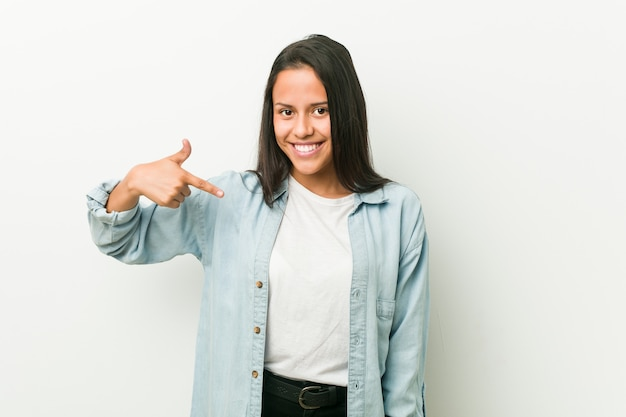 自信を持って自信を持ってシャツを手で指している若いヒスパニック系女性人