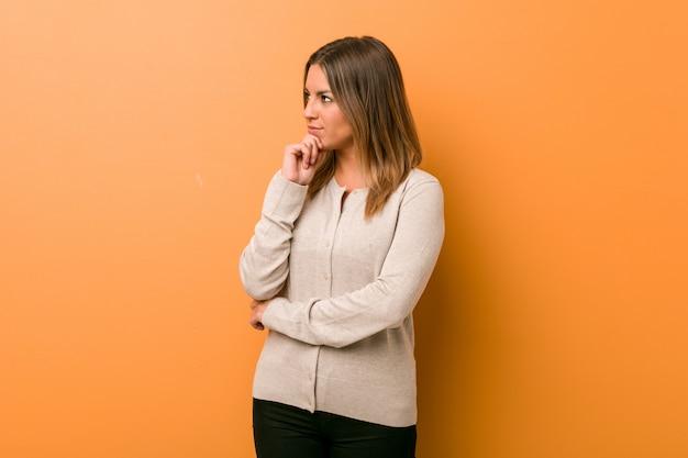 疑わしいと懐疑的な表情で壁に横向きの若い本物のカリスマ的な実在の女性。