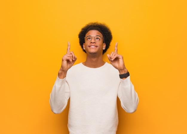 オレンジ色の壁の上の若いアフリカ系アメリカ人の男が何かを見せるために上向きに驚いた