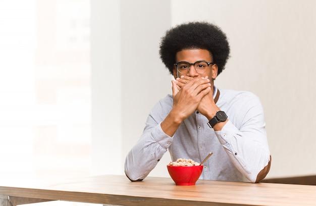 何かについて笑って、手で口を覆っている朝食を持っている若い黒人男性