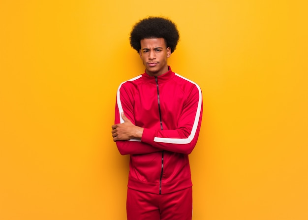 リラックスした腕を交差するオレンジ色の壁の上の若いスポーツ黒人男性