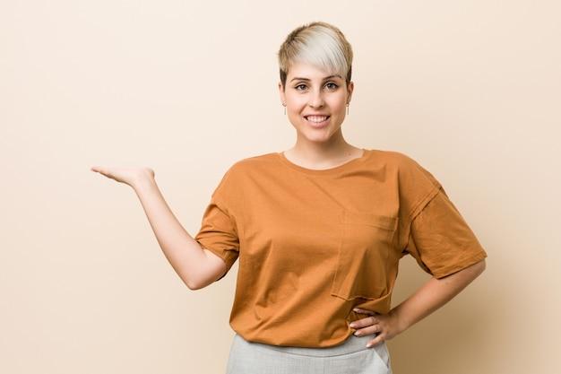 手のひらの上を示し、腰に別の手を握って短い髪の若いプラスサイズの女性。