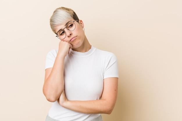 Молодая аутентичная натуральная женщина в белой рубашке, которая чувствует себя грустной и задумчивой, на