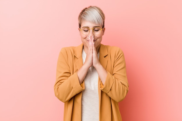 口の近くに祈って手を繋いでいるカジュアルなビジネス服を着ている若い白人女性は自信を感じています。