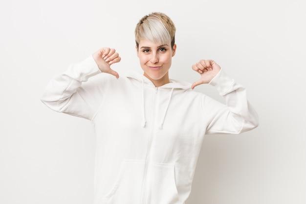 白いパーカーを身に着けている若い曲線の女性は、誇りに思って、自信を持って、次の例です。