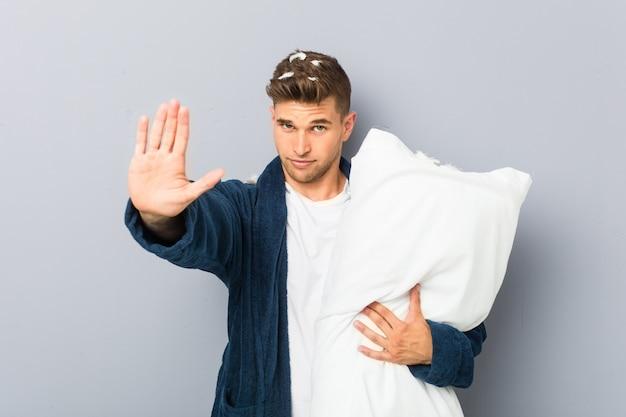 若い男が一時停止の標識を示す伸ばした手で立っている枕を保持しているピジャマを着て、あなたを防ぎます。