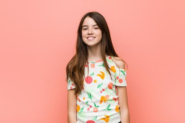 Девушка в летней одежде против стены счастливым, улыбающимся и веселым