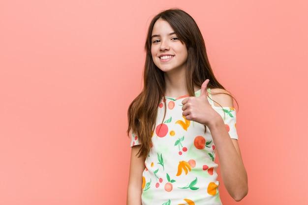 Девушка в летней одежде у стены, улыбаясь и поднимая большой палец вверх