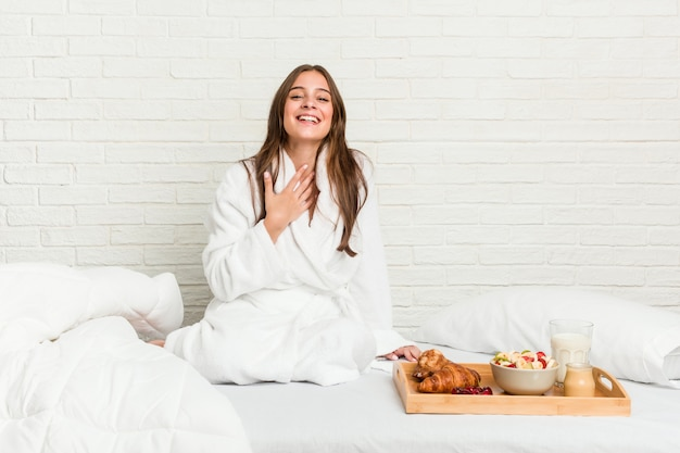 ベッドの上の若い白人女性は大声で笑いながら胸に手をつないでいます。