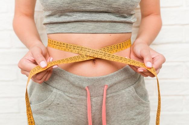 若い白人女性が彼女の腰を測定