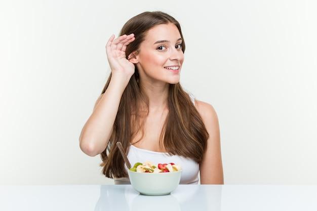 ゴシップを聴こうとしてフルーツボウルを食べる若い白人女性。