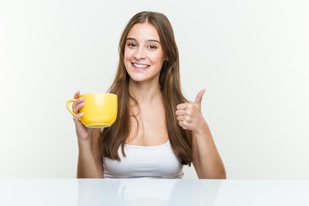 Молодая кавказская женщина держа чашку усмехаясь и поднимая большой палец руки вверх