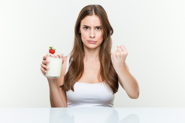 積極的な表情に拳を示すスムージーを保持している若い白人女性。