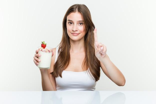 指でナンバーワンを示すスムージーを保持している若い白人女性。