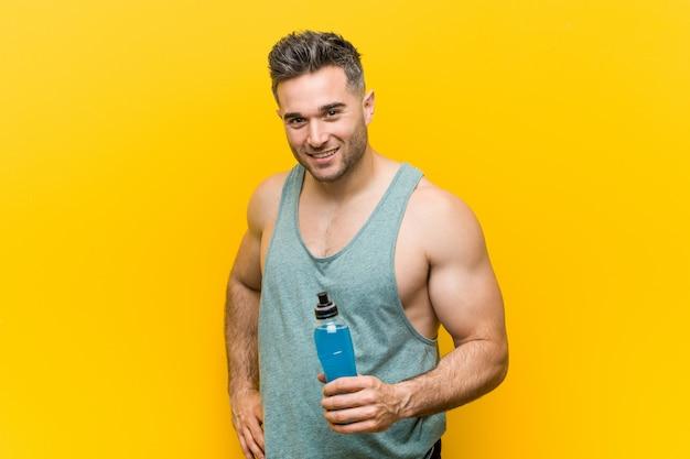 Кавказский мужчина держит энергетический напиток счастливым, улыбающимся и веселым.