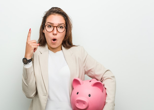 いくつかの素晴らしいアイデア、創造性を持つ貯金を保持している若いヨーロッパビジネス女性。