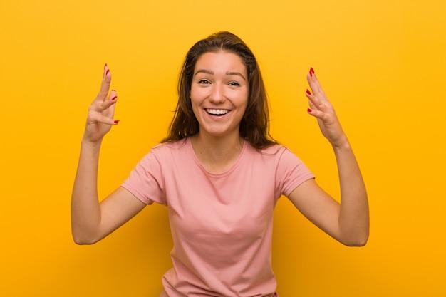 楽しい驚きを受けて興奮して手を上げる黄色で分離された若いヨーロッパの女性。