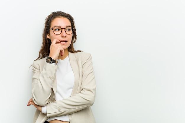 若いヨーロッパのビジネスの女性は、コピーを見て何かについてリラックスして考えています。