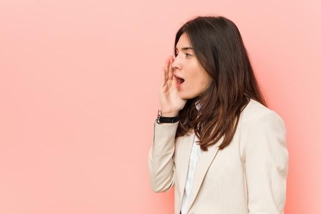 ピンクの叫びと開いた口の近くの手のひらを保持に対して若いブルネットビジネス女性。
