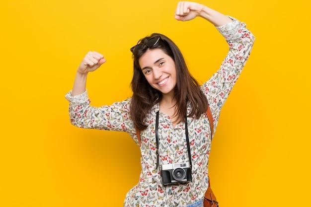 若いブルネット旅行者女性の腕、シンボル女性力で強さのジェスチャーを示す