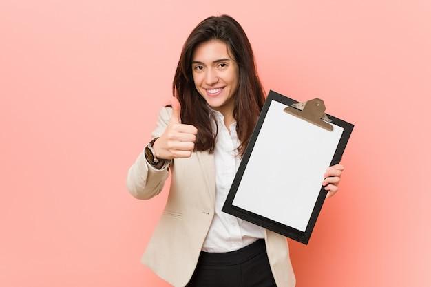 Молодая кавказская женщина держа доску сзажимом для бумаги