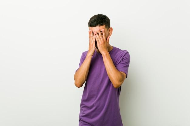 ヒスパニック系の若者は、恐怖と緊張の指の間で点滅します。