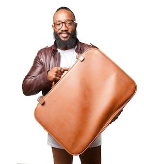 茶色のスーツケースを運ぶ男