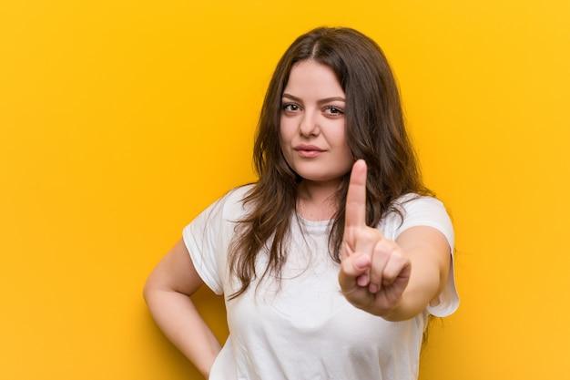 指でナンバーワンを示す若い曲線プラスサイズの女性。